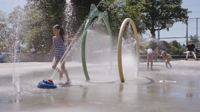 Young kids playing in a water feature at a park