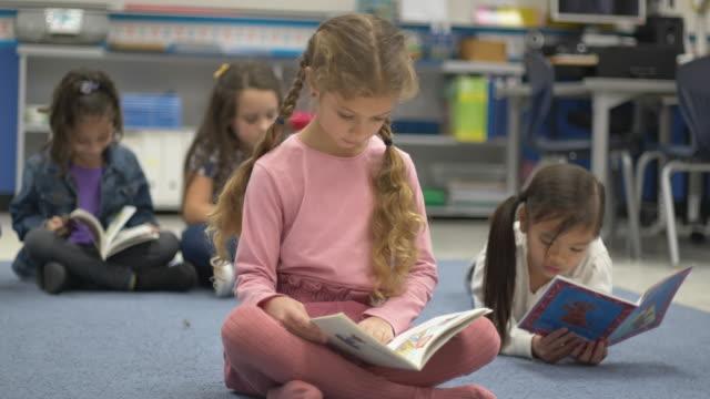vídeos y material grabado en eventos de stock de niños pequeños leyendo en la escuela. - historia