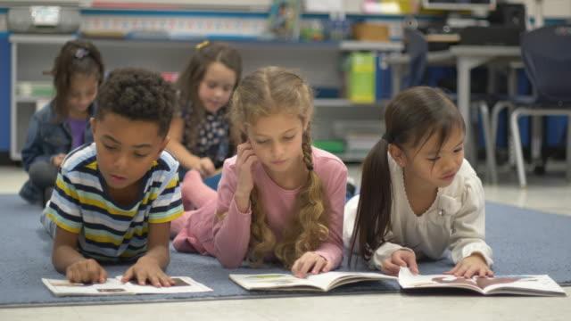vídeos y material grabado en eventos de stock de niños pequeños leyendo en la escuela. - biblioteca