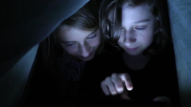 young kids using tablet at night - endast flickor bildbanksvideor och videomaterial från bakom kulisserna