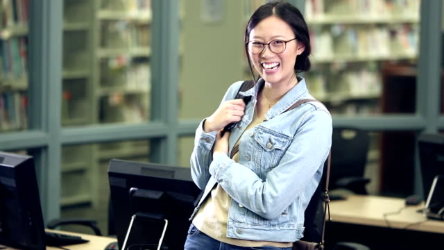 young korean woman in library, carrying book bag - 20 24 years stock videos & royalty-free footage