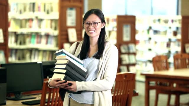stockvideo's en b-roll-footage met jonge koreaanse vrouw in bibliotheek die stapel boeken draagt - carrying