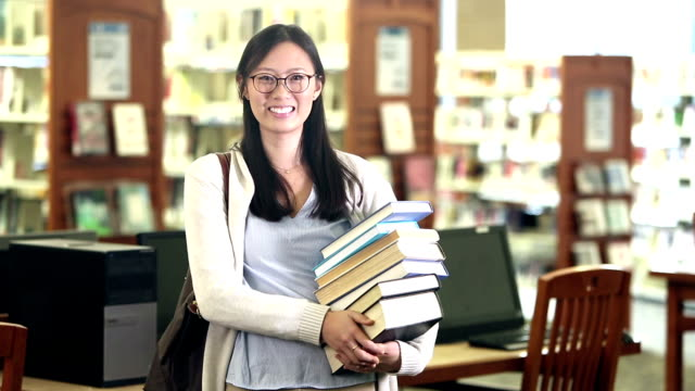 young korean woman in library carrying stack of books - carrying stock videos & royalty-free footage