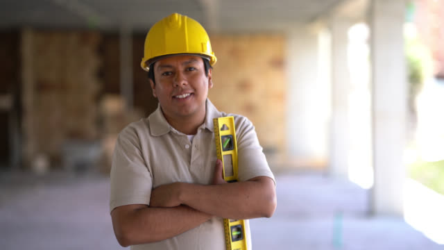young laborer at a construction site walking towards the camera smiling and holding a lever - arms crossed stock videos & royalty-free footage