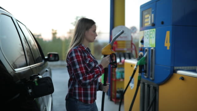 young lady at the gas station - fuel pump stock videos and b-roll footage