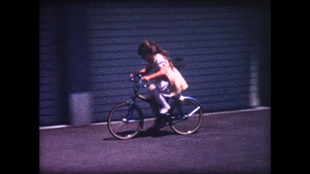 1964 young lady cruising on bicycle in yellow party dress - viewpoint stock-videos und b-roll-filmmaterial