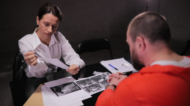 Young lady detective showing photographs to a prisoner in interrogation room