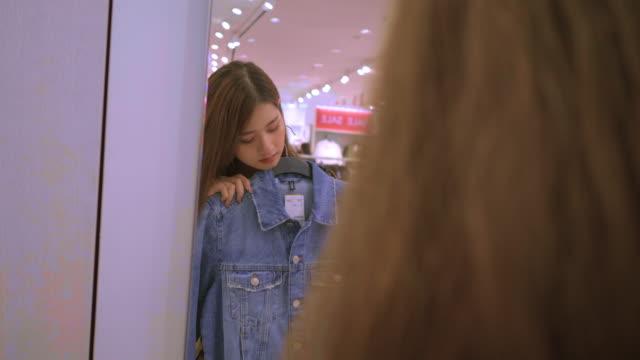 vídeos de stock e filmes b-roll de young lady is choosing jean denim jacket in the shop - jaqueta jeans