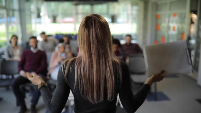 junge dame managersprichtanspricht an kollegen bei vorstandssitzung in firma - redner stock-videos und b-roll-filmmaterial