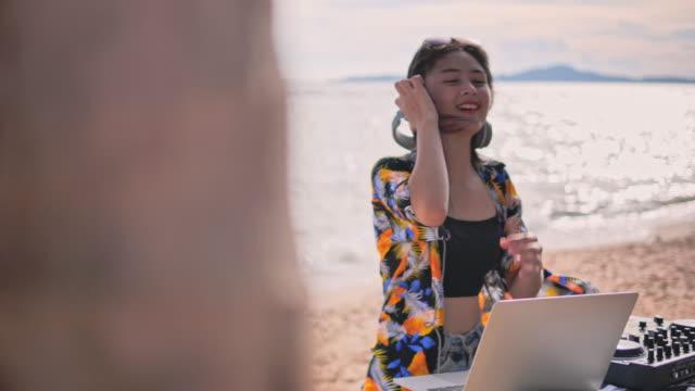 vídeos de stock e filmes b-roll de young lady mix electronic music on the beach - dj