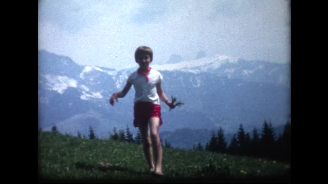 1966 young lady picking flowers with snow-capped mountains behind her