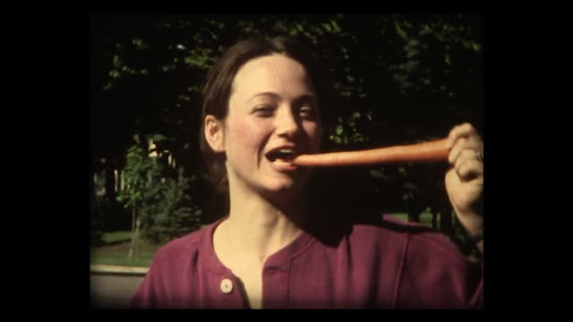 1982 young lady pretends to eat whole carrot - möhre stock-videos und b-roll-filmmaterial