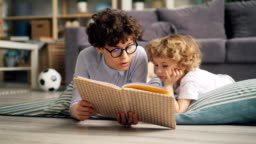 Young lady reading book to her son discussing story lying on floor at home