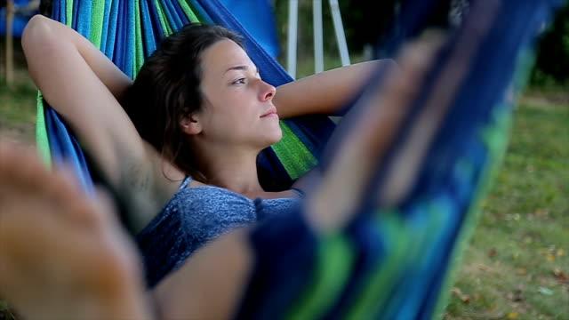 若い女性は、ハンモックで休憩します。性質の概念への脱出します。 - ハンモック点の映像素材/bロール