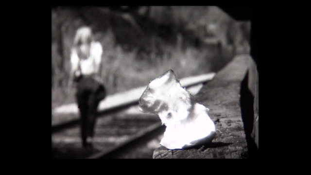 1968 young lady saunters along train track - sulking stock videos & royalty-free footage