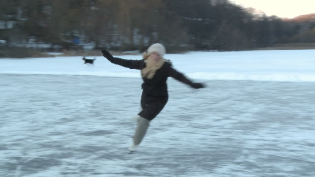 ms ts young lady skating backwards on frozen pond in high park and does spin and  n stops  / toronto, ontario, canada  - ice skating stock videos & royalty-free footage