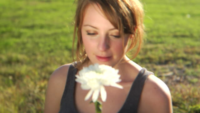 HD CRANE: Young lady smells a flower