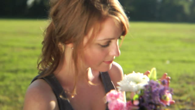 hd crane: a young lady smells flowers - bouquet stock videos and b-roll footage