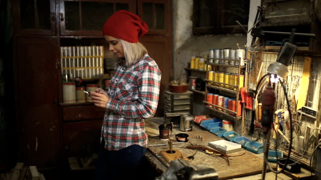 young lady typing message in the work shop - metal worker stock videos and b-roll footage