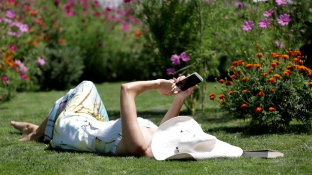 vídeos y material grabado en eventos de stock de señora joven con teléfono móvil en la frente o el patio trasero - jardin
