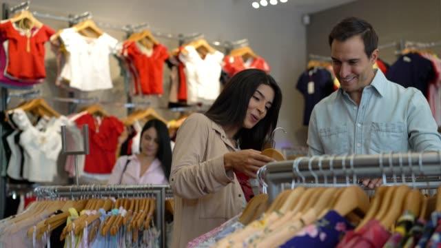 vídeos de stock, filmes e b-roll de jovem casal latino-americano de compras em loja de roupas femininas olhando uma blusa sorrindo - shopping center