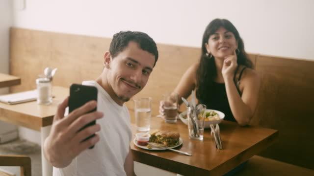 vidéos et rushes de jeune couples latino-américains prenant des selfies au restaurant - influenceur