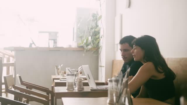 vidéos et rushes de jeunes couples latino-américains utilisant l'ordinateur portatif au café - influenceur