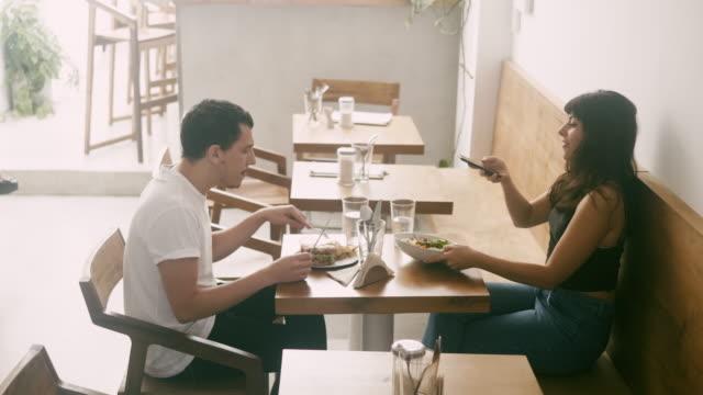 vidéos et rushes de jeune influenceur latino-américain photographiant la nourriture au restaurant - influenceur