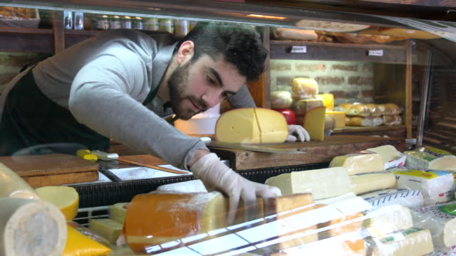 young latin american man arranging the cheese refrigerator display at a delicatessen - consumerism stock videos & royalty-free footage
