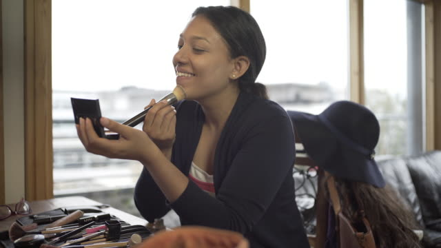 A young Latin American Woman Applying her make up at home.