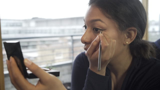 vídeos de stock, filmes e b-roll de a young latin american woman applying her make up at home. - delineador
