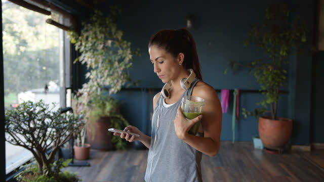 young latin american woman drinking a green juice at the gym while checking messages on smartphone with headphones around her neck - refreshment stock videos & royalty-free footage