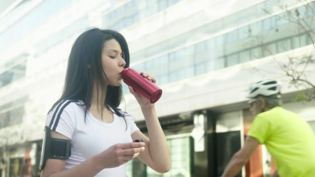 young latin american woman drinks from the reusable water bottle during running session - puerto madero stock videos & royalty-free footage