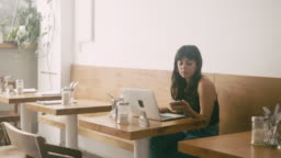 Young latin american woman using smart phone behind the computer at the cafe