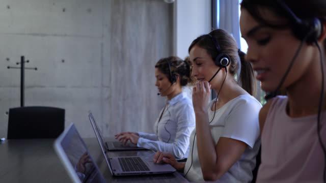 vídeos y material grabado en eventos de stock de jovens mujeres latinoamericanas que trabajan en un centro de llamadas respondiendo llamadas y agregando datos en computadoras portátiles - call center latin