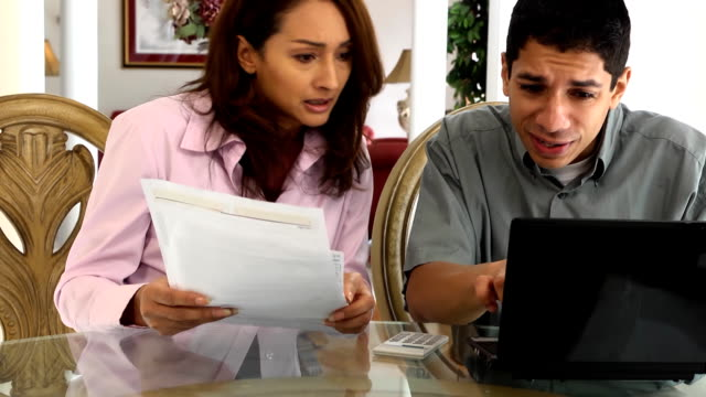 young latin couple do taxes and pay bills - paying taxes stock videos & royalty-free footage