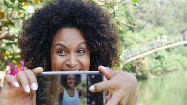 vídeos de stock, filmes e b-roll de mulher latin nova que toma selfies no parque - cabelo encaracolado