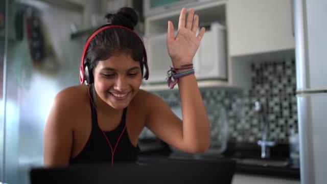 vídeos de stock, filmes e b-roll de mulher latin nova que usa o portátil ao escutar a música em casa - fone de ouvido equipamento de som