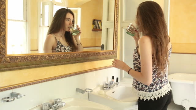 Young Latina woman enters bathroom, applies lipstick then drinks water
