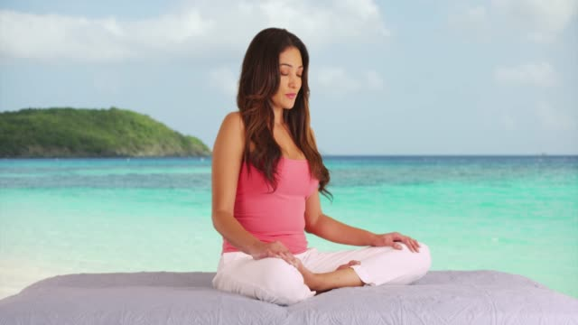 young latina woman meditating on caribbean beach, eyes gently closed - cross legged stock videos & royalty-free footage