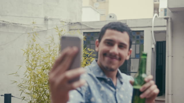 young latin-american male making a selfie with a beer (slow motion) - celebratory toast stock videos & royalty-free footage