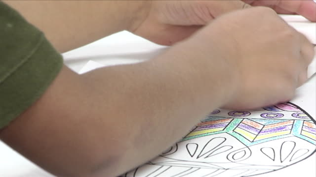 young latino boy hands coloring w/ crayons on printed image of decorated easter egg, changing crayon colors from small box laying bg. hispanic,... - school child stock videos & royalty-free footage