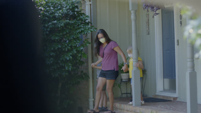young latino family wearing face masks leave their house together holding hands - family with two children stock videos & royalty-free footage