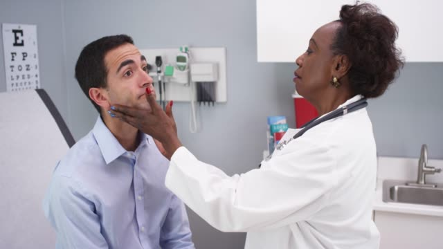 young latino male patient having routine health checkup - lymphatic system stock videos & royalty-free footage