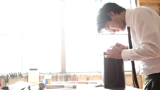 young leather craftsman making a bag - craft点の映像素材/bロール