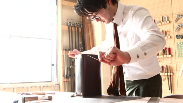 young leather craftsman making a bag - shirt and tie stock videos & royalty-free footage