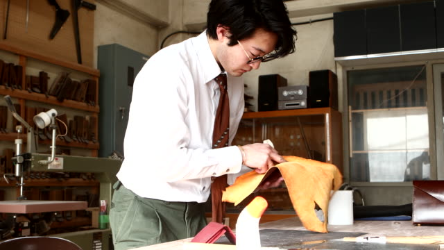 young leather craftsman preparing to make a business card holder - shirt and tie stock videos & royalty-free footage