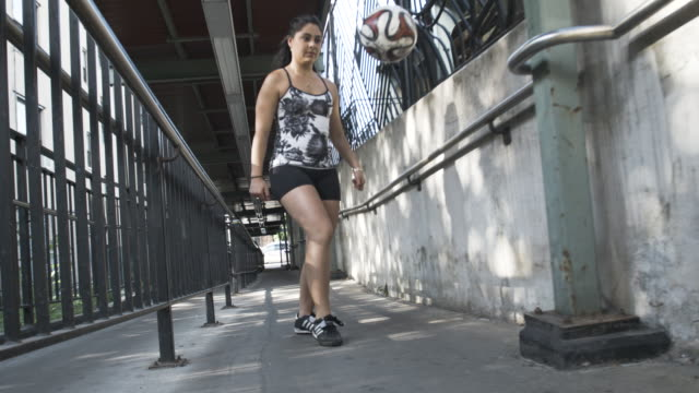 A young Lebanese woman plays soccer in the streets of Brooklyn, New York City - slow motion - summer 2016 - 4k