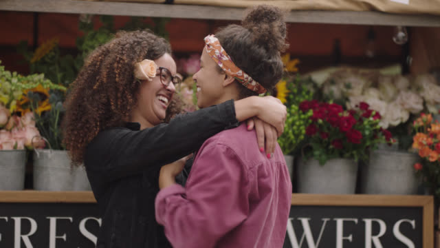 vídeos de stock, filmes e b-roll de young lesbian couple flirts and laughs together in front of a mobile flower truck - rosa cor