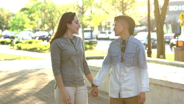 Young lesbian couple holding hands, walking, talking